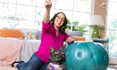 Woman swinging cat toy in front of black and white cat