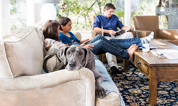 Family sitting on couch with their dog